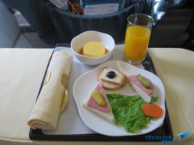 Bữa ăn nhẹ hạng thương gia trên chặng DAD SGN với bánh mì thịt nguội và thạch tráng miệng. Nước hoa quả, sữa, nước ngọt có ga, trà và cà phê cũng được phục vụ. Ảnh: TRAVIP