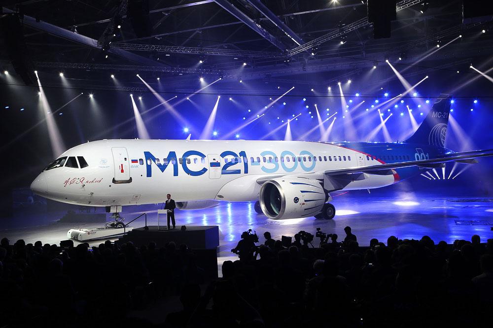 """IRKUTSK, RUSSIA - JUNE 8, 2016: Russia's Prime Minister Dmitry Medvedev (C) speaks at the rollout ceremony for the first Irkut MC-21 jet airliner at an aviation plant of the Irkut Corporation, a United Aircraft Corporation subsidiary. Marina Lystseva/TASS Đîññèÿ. Èđêọ́ñê. 8 è₫íÿ 2016. Ïđǻüåđ-́èíèṇ̃đ ĐÔ Ä́ẹ̀đèé ̀åäâåäåâ (â öåị́đå) âî âđǻÿ öåđǻîíèè âûêạ̀êè ́àăèṇ̃đàëüíîăî ñà́îëạ̊à ̀Ñ-21-300 íà àâèàöèîííî́ çàâîäå êîđïîđàöèè """"Èđêọ́"""". ̀àđèíà Ëûñöåâà/̉ÀÑÑ"""